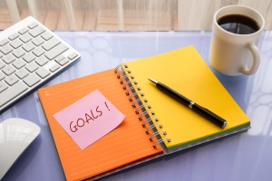 Goals word on note pad stick on blank colorful paper notebook at workspace, year resolution concepts