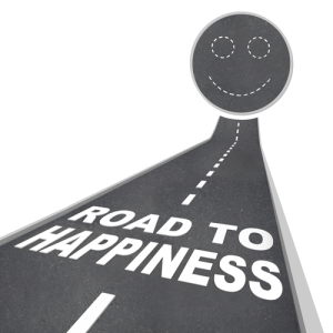 The words Road to Happiness in white letters on a street leading to a smiley face